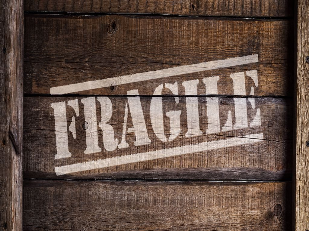 A moving box with the word 'fragile' written on the side - packing fragile items 101