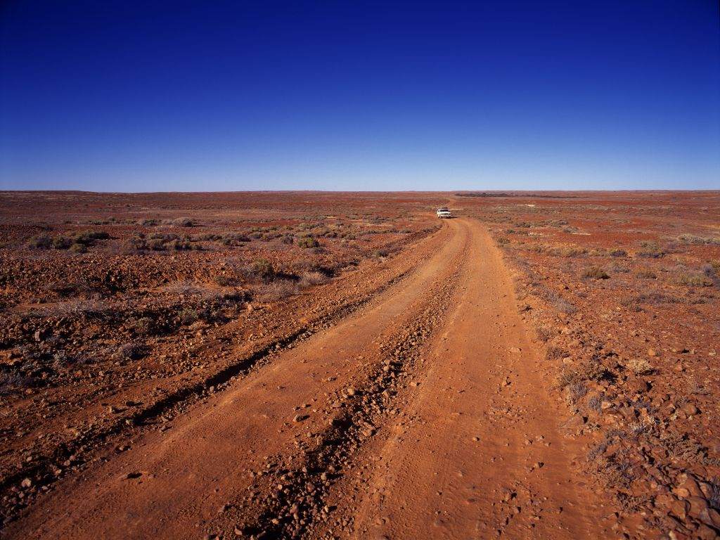 A dirt road in the desert, with tire tracks, symbolizing a road Kensington movers use.