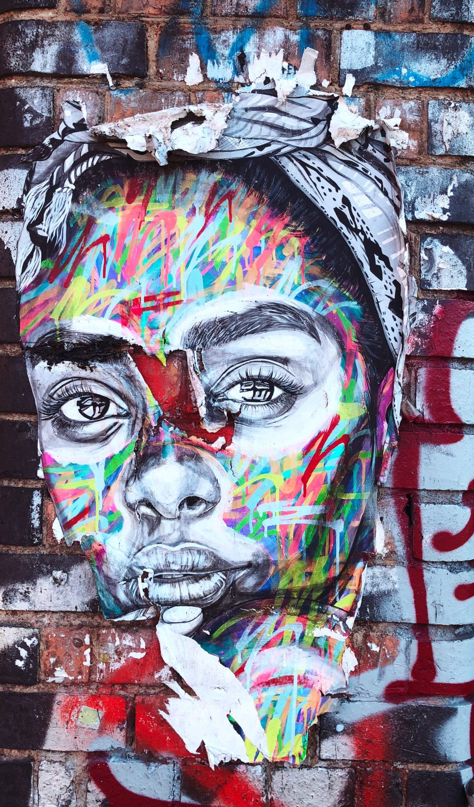 A street art picture of a black woman done in greyscale, and painted over with various colors. The wall itself seems to be crowded with many pieces of art.